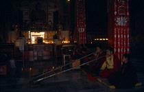 India, Bihar, Bodh Gaya, Karuna Tibetan Buddhist temple interior with monks kneeling on ground to blow long horns.