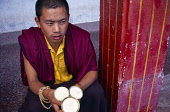 India, Sikkim, Rumtek, Young Buddhist monk wearing prayer beads wrapped around wrist and purple and yellow robes holding unlit yak butter candles.