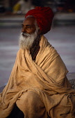 India, Uttar Pradesh, Rishikesh, Elderly Hindu male pilgrim with red turban and grey beard  wrapped in blanket.