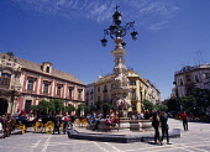 Spain, Andalucia, Seville, Santa Cruz District  Plaza Virgen de los Reyes  Palacio Arzobispal on the left  fountain  horse carriages  people.