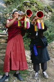 China, Tibet, Lhasa, Drak Yerpa Monastery complex, Monk and layman blowing trumpets with rainbow tassles hanging from them.