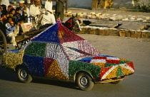 Pakistan, Punjab, Rawalpindi, Wedding car covered in brightly coloured tinsel passing horse drawn cart on street.
