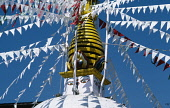 Nepal, Kathmandu Valley, Swayambhunath, Central temple stupa painted with the eyes of Buddha and hung with red and white flags.