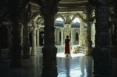 India, Rajasthan, Mount Abu, Interior of Jain temple with elaborately carved roof and supporting pillars framing female visitor.