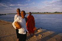 Cambodia, Phnom Penh, Buddhist monk and nuns on waterside.