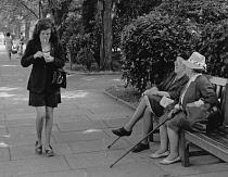 England, Merseyside, Southport, Woman walking along Lord street lighting her cigarette, 1970.