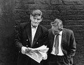 England, Merseyside, Liverpool, Two men reading the Daily Mirror newspaper in the street, 1968.