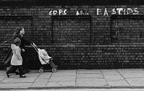 England, Merseyside, Liverpool, Graffiti with Cops are Bastids written on brick wall as children walk by, 1972.