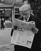 England, Merseyside, Bootle, Elderly man with flat cap and glasses reading the Daily Mail newspaper 1st May 1971.