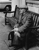 England, Merseyside, Southport, Old man with Pomeranian dog sat on bench on Christmas Eve 1968.