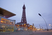 England, Lancashire, Blackpool, Seafront promenade with Tower at dusk.