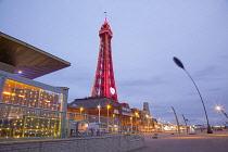 England, Lancashire, Blackpool, Seafront promenade with Tower illuminated at dusk.