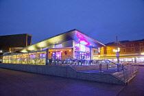 England, Lancashire, Blackpool, Seafront promenade with restaurant illuminated at dusk.