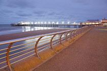 England, Lancashire, Blackpool, Seafront promenade with North Pier illuminated at dusk.