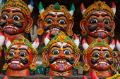 India, Pondicherry, Display of masks of an evil god at an arts and crafts stall in market.