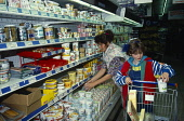 Holland, Supermarket interior with woman and young girl placing food items into trolley.