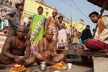 India, Uttar Pradesh, Varanasi, A bereaved family at a puja on Kedar Ghat.