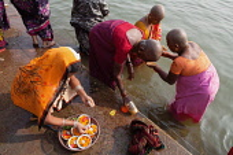 India, Uttar Pradesh, Varanasi, Female pilgrims pray and make offerings at the River Ganges.