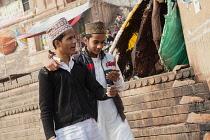 India, Uttar Pradesh, Varanasi, Muslim men look at their iphone on the ghats.