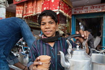 India, Uttar Pradesh, Varanasi, A chai boy serving tea.
