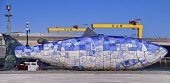 Northern Ireland, Belfast, Donegall Quay, The Big Fish Sculpture by John Kindness with the scales of the fish represented by pieces of printed blue tiles which show details of Belfasts history, in the...