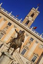 Italy, Lazio, Rome, Piazza del Campidoglio designed by Michelangelo, Angular view of the statue of the Roman Emperor Marcus Aurelius on horseback with the clock tower of Palazzo Senatorio in the backg...