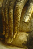 Thailand, North, Sukhothai, Wat Si Chum. Detail of hand of massive seated Buddha figure scattered with pieces of gold leaf by worshippers.