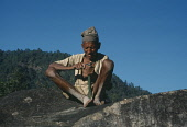 Nepal, Bumlingtar, Old man sitting on rock carving with knife.