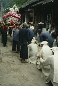 China, Guangxi Province, Fuli, Funeral procession mourners kneeling in front of flower covered coffin carried behind. .