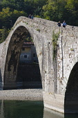Italy, Tuscany, Lucca, Garfagnana, Bagni di Lucca, Devil's aka Maddalena's Bridge with people walking over the high arch