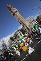 Ireland, North, Belfast, St Patricks Day parade passing the Albert clock on the corner of High Street and Victoria Street.
