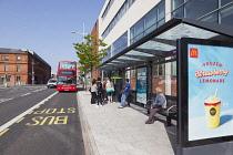 Ireland, North, Belfast, Titanic Quarter, Tourists at bus stop awaiting tour bus.