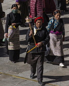 Tibetan Buddhist pilgrims from the Kham region of eastern Tibet circumambulating around the Jokhang Temple in Lhasa, Tibet.  A Khamba man with his red headdress leads his family with a prayer wheel.