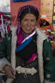 A Khamba Tibetan woman from the Kham region of eastern Tibet on a pilgrimage to visit holy sites in Lhasa, Tibet.  She is wearing a traditional heavy sheepskin-lined chupa or chuba coat.