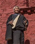 A Tibetan Buddhist pilgrim from the Kham region of eastern Tibet at the Drepung Monastery near Lhasa, Tibet.  He is wearing the heaving sheepskin-lined chuba or chupa coat and is carrying his mala ros...