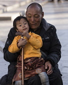 A grandfather and his grandchild sit at Barkhor Square in Lhasa, Tibet.