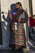 A Khamba Tibetan woman from the Kham region of eastern Tibet on a pilgrimage to the Jokhang Temple in Lhasa, Tibet.  She is wearing a traditional heavy sheepskin-lined chupa or chuba coat and gangdian...