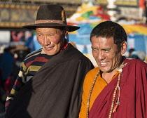 A Tibetan Buddhist pilgrim from the Kham region of eastern Tibet and a monk circumambulating around the Jokhang Temple in Lhasa, Tibet.