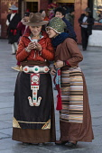 Two young Khamba Tibetan women from the Kham region of eastern Tibet on a pilgrimage to visit holy sites in Lhasa, Tibet.  One is wearing a western-style felt hat, which is very popular in the Kham re...