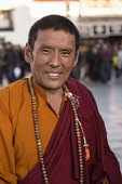 A Tibetan Buddhist monk at the Jokhang Temple in Lhasa, Tibet.  Around his neck are his mala rosary beads.