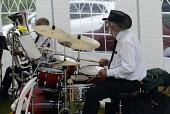 Music, Percussion, Drums, Drummer playing with band in a tent.