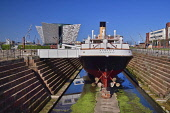 Ireland, County Antrim, Belfast, Titanic Quarter, Titanic Belfast visitor attraction with the SS Nomadic a former tender for the White Star Line shipping company  that was once used to transfer mail a...