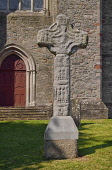 Ireland, County Down, Downpatrick, Replica of Downpatrick High Cross with the Cathedral Church of the Holy Trinity also known as Down Cathedral in the background.