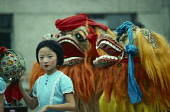 China,  Chinese New Year Dragon dancers and young girl.