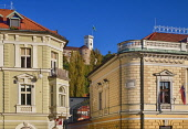 Slovenia, Ljubljana, The facade of the Philharmonic Hall in Kongresni Trg on right with Ljubljana Castle  high in the background.