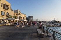 Israel, Jaffa, Old Jaffa, Tourists on the promenade along the seafront buildings at the Old Jaffa Port, Namal Yafo.