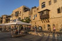 Israel, Jaffa, Old Jaffa, Tourists on the promenade along the seafront buildings at the Old Jaffa Port, Namal Yafol.