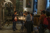 Israel, Jerusalem, Christian pilgrims visiting the Church of the Holy Sepulchre in the Christian Quarter. The Old City of Jerusalem and its Walls is a UNESCO World Heritage Site. This church was built...