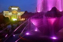 Romania, Timis, Timisoara, Colourfully lit fountain and Opera House/National Theatre illuminated at nighti, Piata Victoriei , old town.