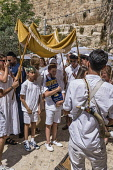 Israel, Jerusalem, Jewish Quarter, A bar mitzvah procession moves toward the entrance to the Jewish Quarter of the Old City. One young boy carries the Torah scrolls.